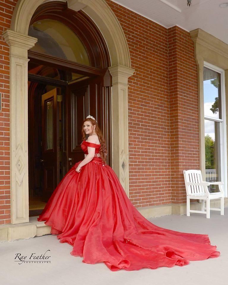 Bride in Red dress entering mansion for wedding