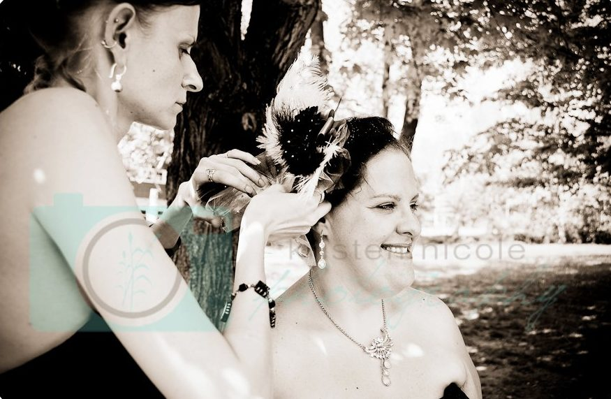 bridesmaid helping switch out brides veil