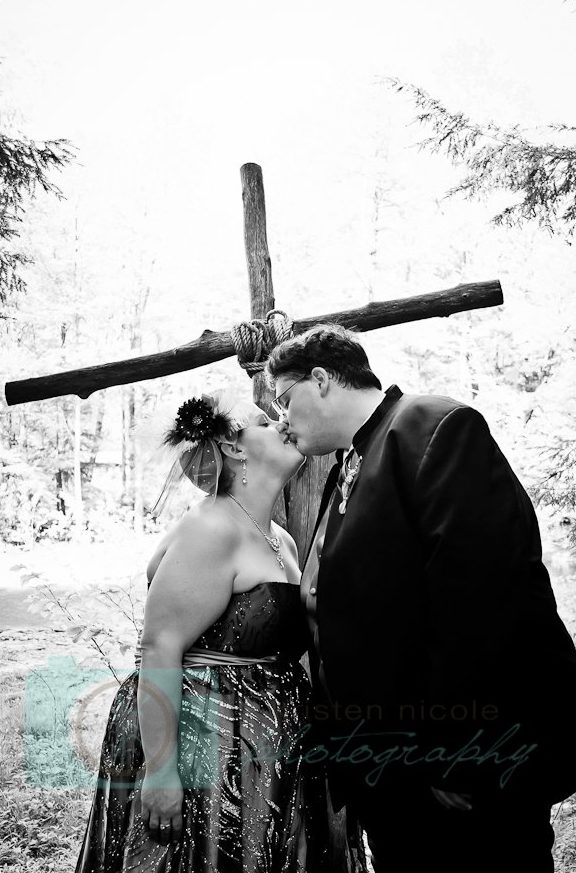 Bride and groom kissing by cross