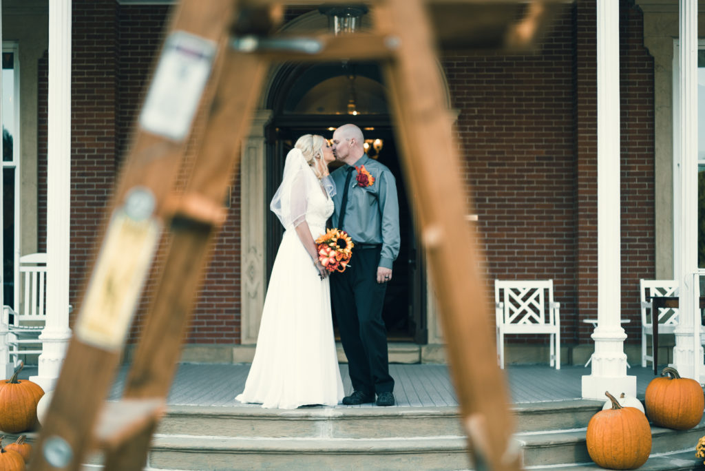 bride and groom kiss under a ladder
