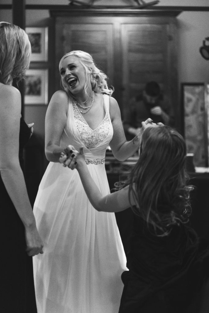 bride and flowergirl dancing