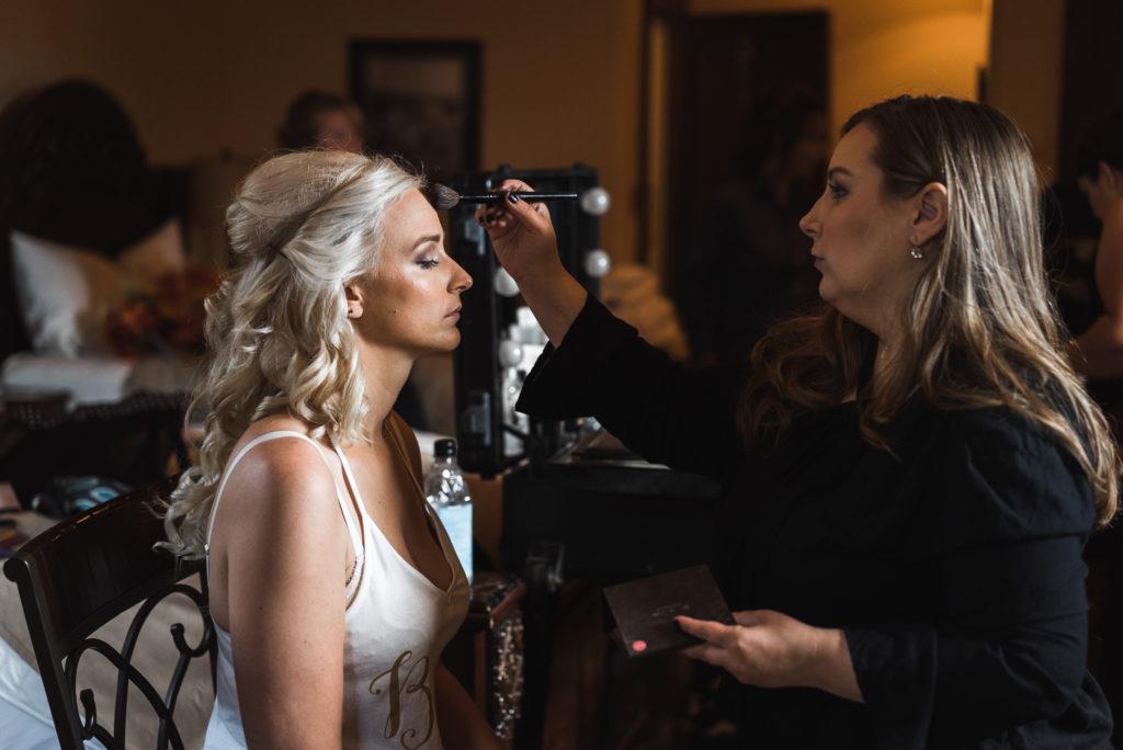 Bride getting into makeup