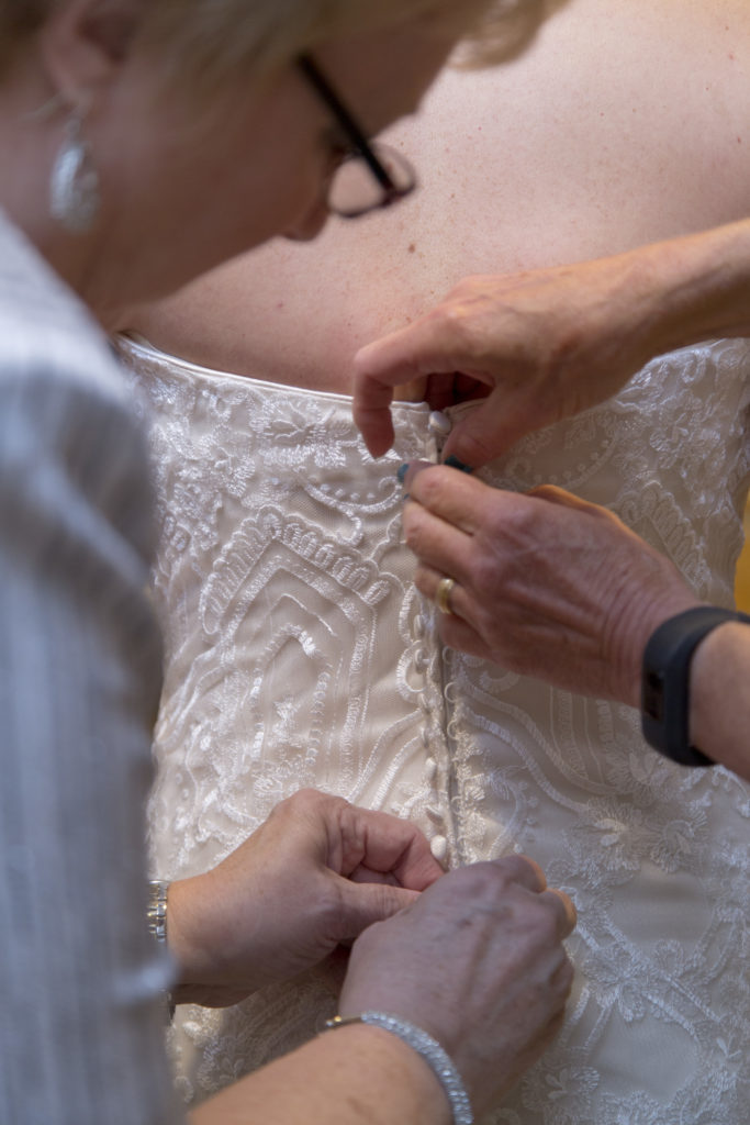 getting bride into her wedding dress