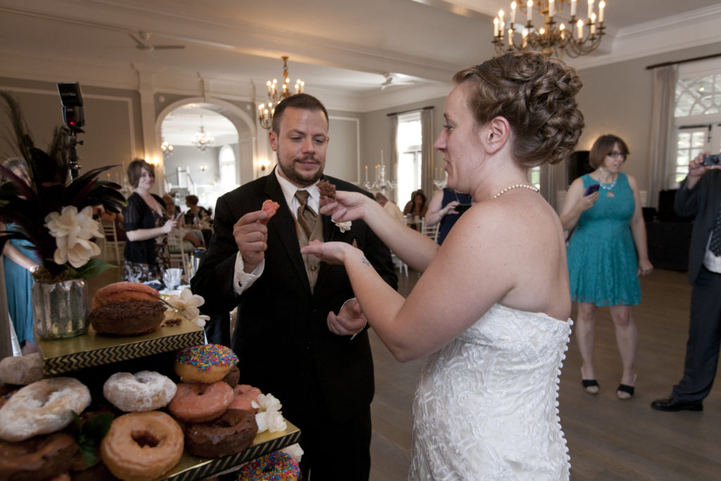 bride and groom eating donuts