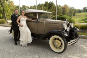 bride and groom by old car