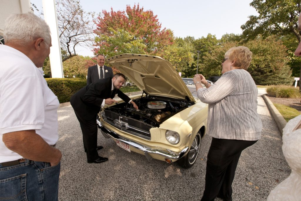 groom by old car cleveland wedding planner